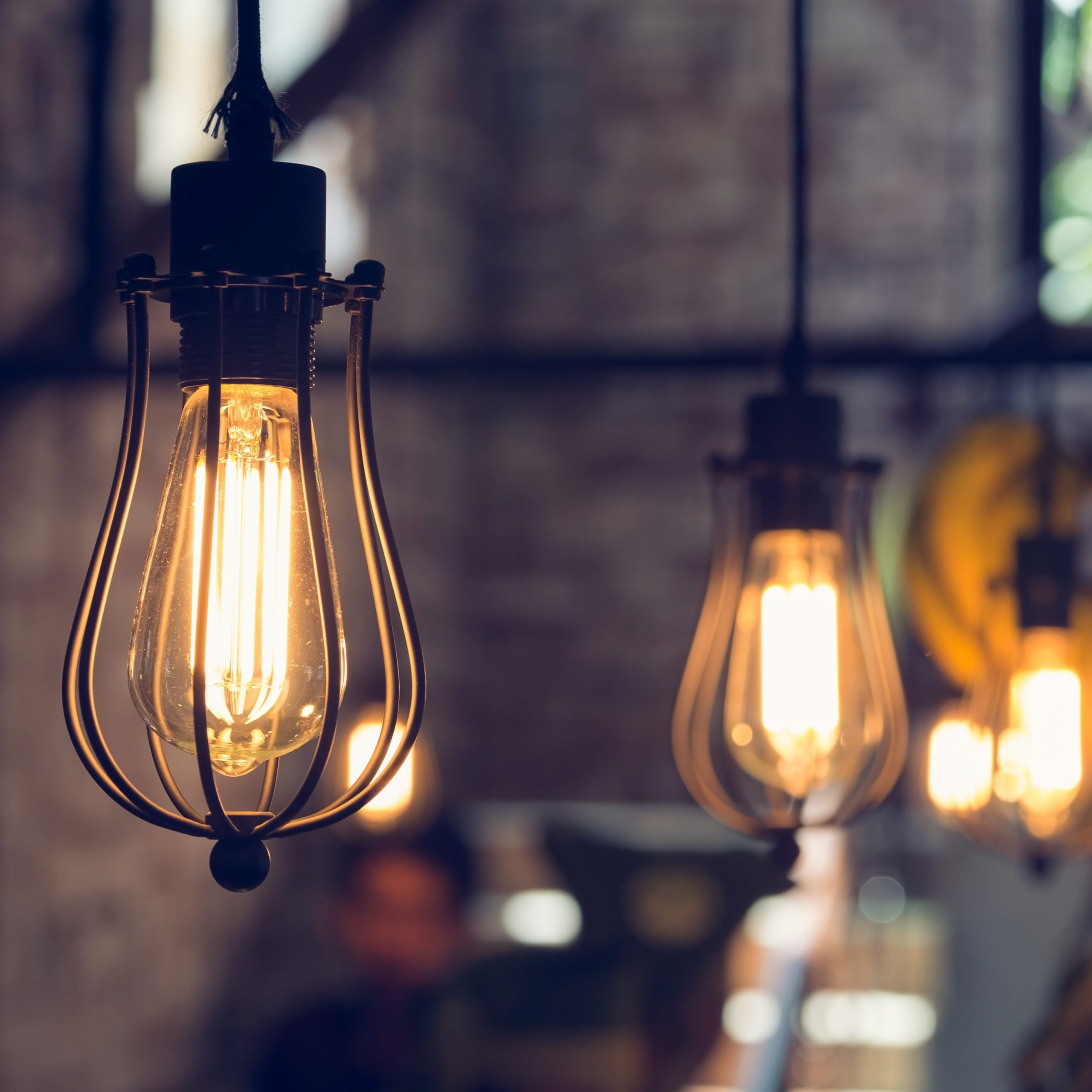 industrial lighting fixtures hanging in a brick kitchen covered by a premium home warranty plan