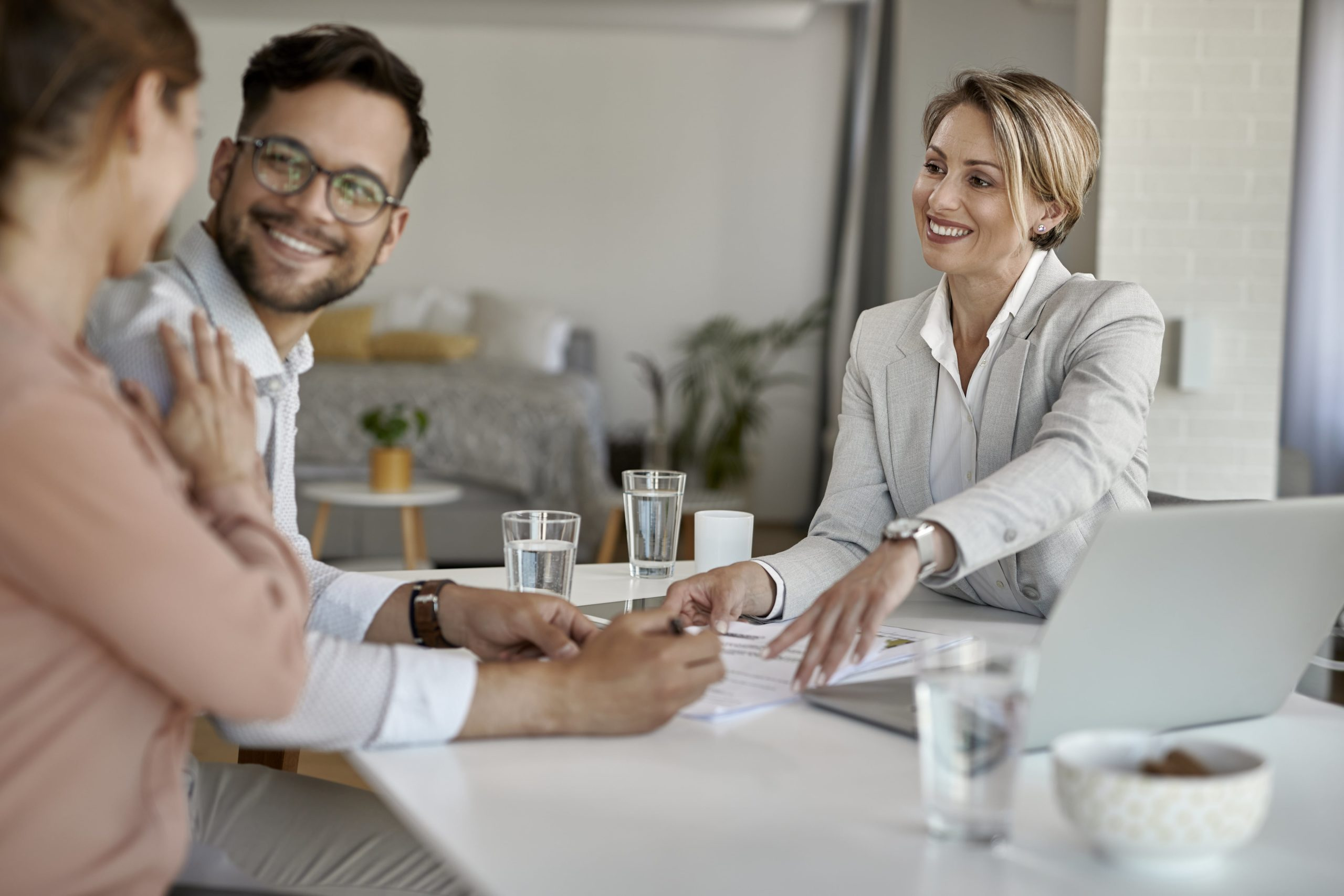 Real estate agent goes over paperwork for a Premium Home Warranty with a happy couple of homeowners.